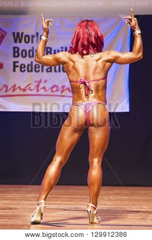MAASTRICHT THE NETHERLANDS - OCTOBER 25 2015: Female fitness model flexes her muscles and shows her best physique in a back double biceps pose on stage at the World Grandprix Bodybuilding and Fitness of the WBBF-WFF