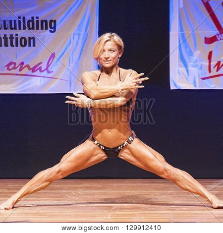MAASTRICHT THE NETHERLANDS - OCTOBER 25 2015: Female fitness model Gerbel Mikk flexes her muscles and shows her best physique in a front pose on stage at the World Grandprix Bodybuilding and Fitness of the WBBF-WFF