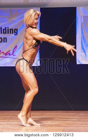 MAASTRICHT THE NETHERLANDS - OCTOBER 25 2015: Female fitness model Gerbel Mikk flexes her muscles and shows her best physique in a side pose on stage at the World Grandprix Bodybuilding and Fitness of the WBBF-WFF