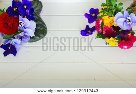 Posy of violets, pansies, daisies  and ranunculus on white wooden background with copy space