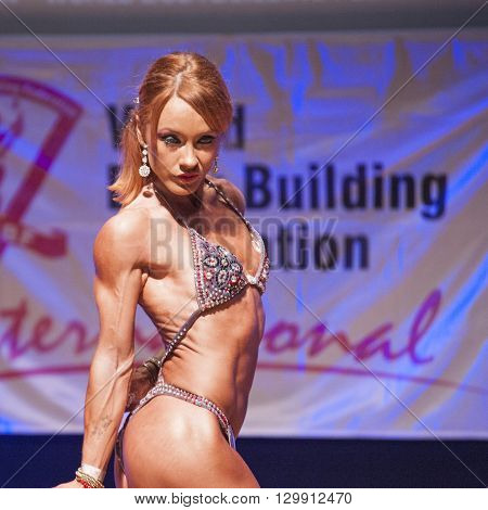 MAASTRICHT THE NETHERLANDS - OCTOBER 25 2015: Female fitness model flexes her muscles and shows her best physique in a triceps pose on stage at the World Grandprix Bodybuilding and Fitness of the WBBF-WFF on October 25 2015 at the MECC Theatre