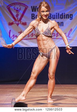 MAASTRICHT THE NETHERLANDS - OCTOBER 25 2015: Female fitness model flexes her muscles and shows her best physique in a front pose on stage at the World Grandprix Bodybuilding and Fitness of the WBBF-WFF on October 25 2015 at the MECC Theatre