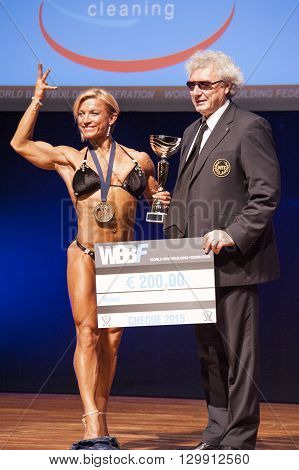 MAASTRICHT THE NETHERLANDS - OCTOBER 25 2015: Female bodybuilder Gerbel Maikk celebrates her victory on stage with the official at the World Grandprix Bodybuilding and Fitness of the WBBF-WFF on October 25 2015 at the MECC Theatre in Maastricht