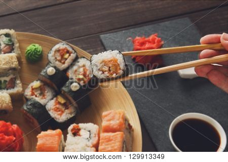 Japanese food restaurant, sushi maki roll plate, platter set. Hand take roll. Set for two with chopsticks, ginger, soy, wasabi. Sushi at rustic wood background and black stone. POV at black. Closeup.