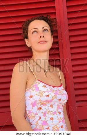 Woman stand near  door from red horizontal jalousies and looks up
