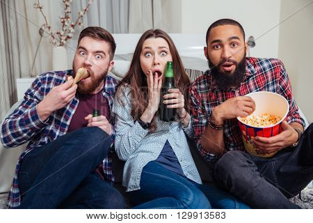 Multiracial group of frightened shocked young people drinking beer with pizza and watching tv