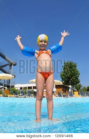 Girl stands in  day-time on skirting in  pool near  hotel and with gladness lifted   hand, underwater package shot