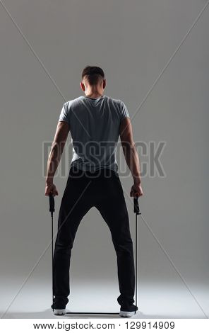 Rear view portrait of a fitness man workout with expander over gray background