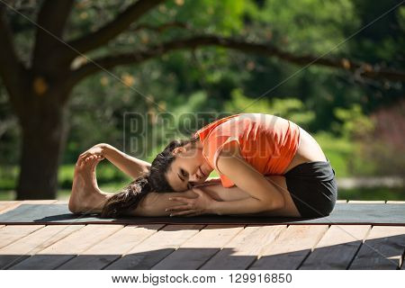 Beautiful girl is engaged in yoga on the wooden terrace on the nature background. She seated forward bend on the black yoga mat. Her head lies on the left knee, left hand is on left leg, right hand is on the feet. She looks into the camera. She wears blac