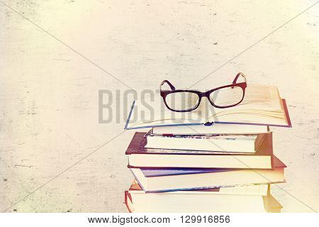 a pile of books and eyeglasses on scratched background