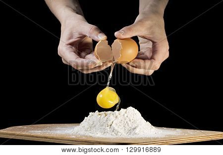 female hands breaking a raw egg on black background