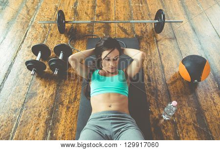 Woman making abs training on the gym floor. Concept about fitness and sport training