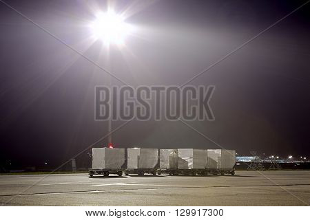Air cargo containers on carts at night