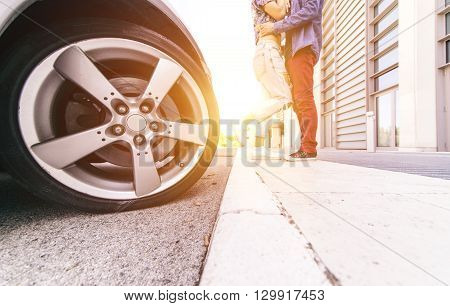 Couple kissing outside their car. Focus on the car wheel