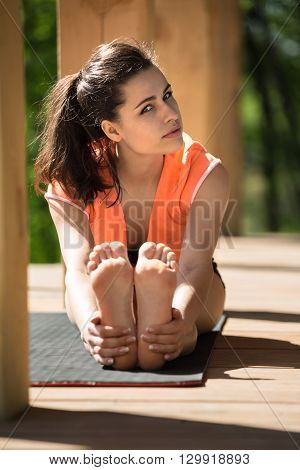 Barefoot girl is engaged in yoga on the wooden terrace on the nature background. She seated forward bend on the black yoga mat. She holds her feet with her hands. She looks into the camera with partially turned head. She wears black shorts and orange t-sh