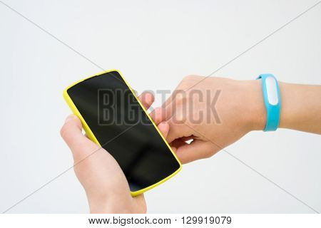 Female Hand Holding Yellow Mobile Phone And Blue Fitness Tracker On A White Background