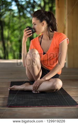 Amazing girl sits on the black yoga mat on the wooden terrace on the nature background. Her head is turned to the right, right foot stands on the mat, left leg lies on the mat and right foot, left hand is on left leg. She drinks from the black cup in her
