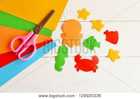 Sheets of colored paper, scissors, glue, paper fish and sea creatures. DIY concept. Easy kids craft idea. Paper craft