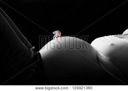 color key of pacifier on pregnant mother belly at black background