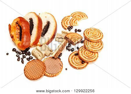 There are Pieces of Roll with Poppy Seed and Cookies,Halavah,Chocolate Peas,Tasty Sweet Food on the White Background,Top View