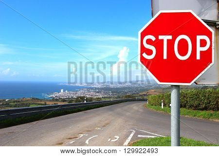 Stop sign on the empty road leading to Lagoa and Ponta Delgada, Sao Miguel island, Azores, Portugal