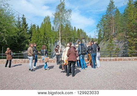RUSKEALA, KARELIA, RUSSIA-MAY 14, 2016: Tourists and guide in The Mountain Park