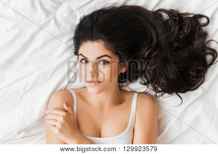 topview portrait of Young woman lying on bed