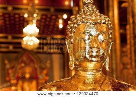 Golden head of meditating Buddha inside the historical Thai temple in city Chiang Mai Thailand