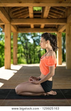Brunette girl sits sideways on her heels on the black yoga mat on the wooden terrace on the nature background. She holds her hands on her legs. She looks in front of herself. She wears black shorts and orange t-shirt. Outdoors. Vertical.