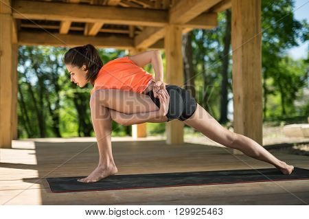 Pretty girl makes low lunge with left leg forward on the black yoga mat on the wooden terrace on the nature background. She holds her hands together on her back and left hand is clasping left leg. She looks at the floor with parted lips. She wears orange