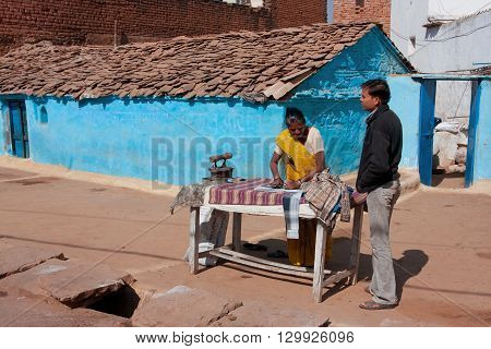 ORCHHA, INDIA - DEC 20, 2012: Indian woman irons clothes coal iron outdoor at the bright day on December 20, 2012 in Orchha Madhya Pradesh India. Orchha had population of 10000. Females constitute 47 perc