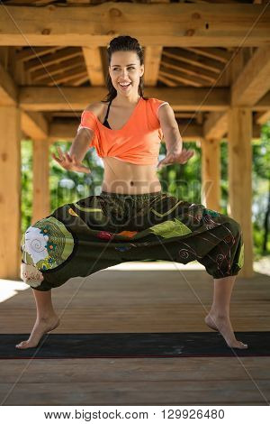 Smiling girl does sumo squats on the black yoga mat on the wooden terrace on the nature background. She stands on the toes and holds her hands stretched forward. She looks to the side. She wears orange t-shirt and the wide olive pants with images. Sunligh