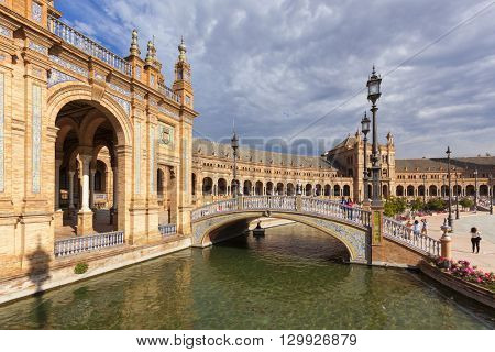 Seville, Spain - April 30, 2016: Plaza de Espana, view from a bridge across the canal. Tourists visiting the famous square.