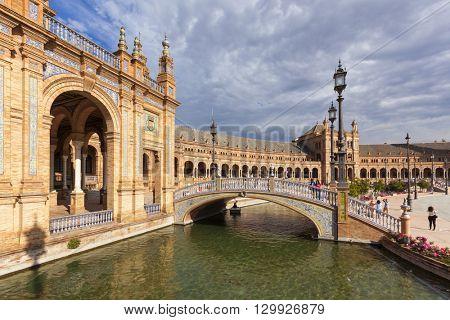 Seville, Spain - April 30, 2016: Plaza de Espana, view from a bridge across the canal. Tourists visiting the famous square.