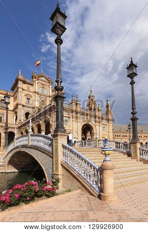 Seville, Spain - April 30, 2016: Plaza de Espana, view beneath a bridge crossing the canal in front of center part of the pavilion. Tourists visiting the famous square.