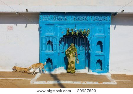 MADHYA PRADESH, INDIA - DEC 20, 2012: Woman in ethnical clothes leaves the house on December 20, 2012 in Orchha Madhya Pradesh India. Madhya Pradesh is the second largest indian state with 75 mill.people