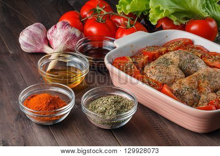 chicken legs in bowl with marinad and spices
