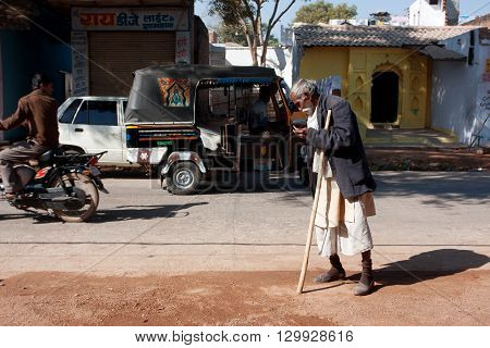 ORCHHA, INDIA - DEC 20, 2012: Indian senior man walk the street at the sunny day on December 20, 2012 in Madhya Pradesh, India. 60-plus age group in India will increase to 100 million people in 2013