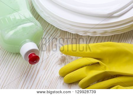 Detergent, dishes and latex gloves on wooden background