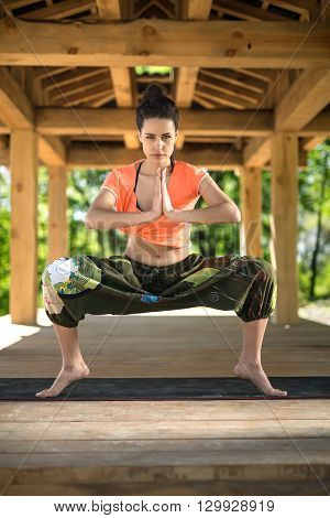Attractive girl does sumo squats on the black yoga mat on the wooden terrace on the nature background. She stands on the toes and holds her palms  together. She looks into the camera with parted lips. She wears orange t-shirt and the wide olive pants with