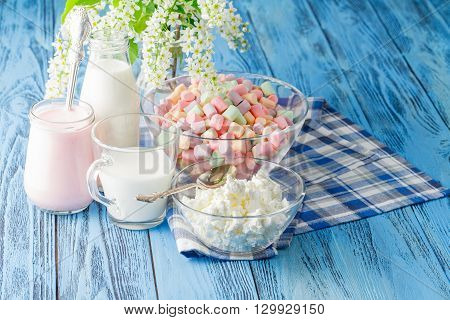 Colorful marshmallows in a glass jar and blue napkin