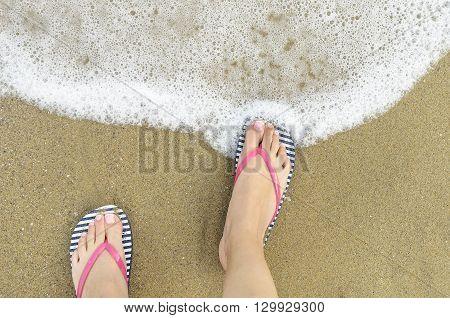 Female feet in shales and sea foam.