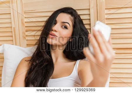 Beautiful young woman is making a selfie using a smart phone and smiling while sitting in bed