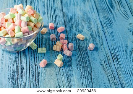 marshmallow in bowl on blue wooden vibrant background
