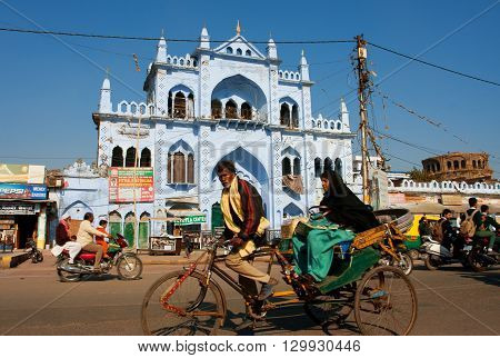 LUCKNOW, INDIA - DEC 18, 2012: Cycle rickshaw takes an elderly Muslim woman on a beautiful street with blue houses on December 18, 2012 in Lucknow, India. Lucknow in Uttar Pradesh state has pop. of 4588455