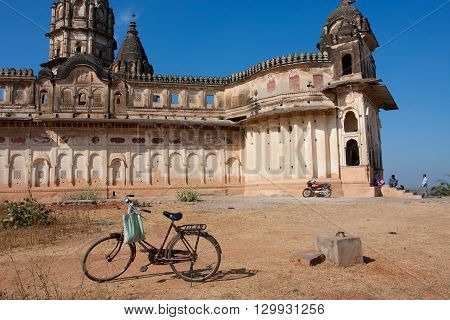 ORCHHA, INDIA - DEC 20, 2012: Cycle and the motorbike left by the hindu worshipers near Lakshmi Narayana Temple on December 20, 2012 in India. The temple was built by King Veer Singh in 1622