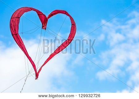 Red kite heart in the blu skye