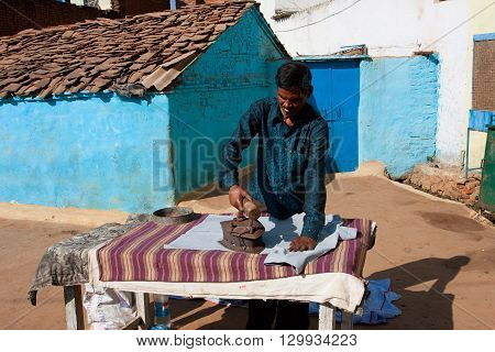 ORCHHA, INDIA - DEC 20, 2012: Asian man irons clothes by the coal iron outdoor at the sunny day on December 20, 2012 in Orchha Madhya Pradesh India. Orchha had a population of 10000. Males constitute 53 perc.
