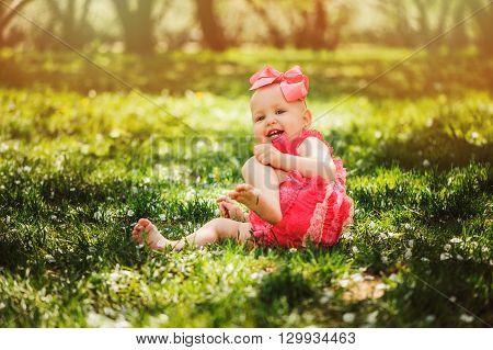 cute happy baby girl in funny pink romper walking outdoor in spring garden. Happy childhood concept