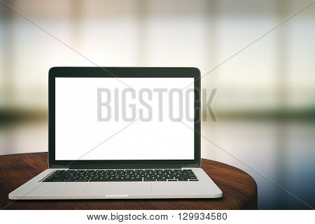Dark wooden tabletop with blank laptop on blurry interior background. Mock up 3D Rendering
